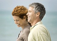 Mature couple smiling by seaside