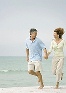 Mature couple running on beach, hand in hand