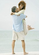 Mature couple, man picking up woman on beach
