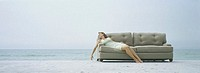 Woman reclining on sofa, on beach