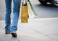 Person walking with shopping bags, low section