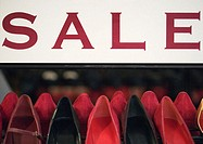 Sale sign over rack of shoes