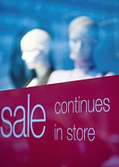 Shop window with sign saying 'sale continues in store'