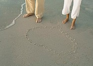 Couple standing by heart drawn in sand, view of knee down