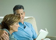 Mature couple looking at book together