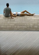 Couple by edge of pool, woman lying down and man sitting