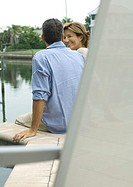 Couple sitting by edge of water