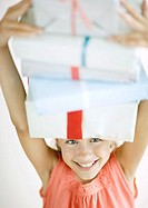 Girl holding stack of presents on head