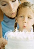 Mother and girl blowing out candles on birthday cake