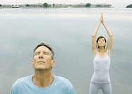 Couple doing relaxation exercises by edge of water
