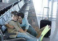 Woman sitting with son in airport lounge