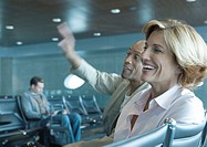 Man and woman sitting in airport lounge, laughing