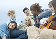 Group of young people hanging out, one playing guitar