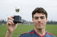 Footballer with miniature trophy