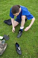 Footballer putting on his boots