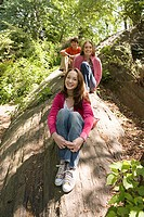 Three teenagers sitting in a forest