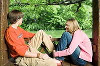 Teenage couple on bench near a lake