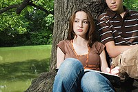 Teenagers sitting by a tree