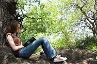 Girl writing in a notebook near a tree