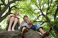Teenage couple relaxing on a rock
