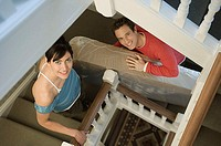 Couple carrying mattress up stairs (thumbnail)