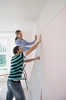 Couple putting up wallpaper