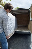 Man moving mattress from van