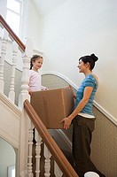 Mother and daughter carrying box up stairs