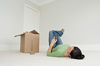 Woman lying on floor with cellphone and cardboard box