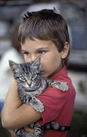 Little child in a red shirt with a little cat on his arms