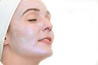 Young woman caring about her face with a creme mask