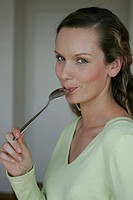 A young woman tastes honey while she looks at the camera.