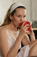 A blonde woman in slip having a cup of coffee