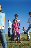 Teens and preteens of many different ages standing around separately in field