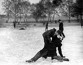 A male ice skater catches another man as he falls over on the ice. Photograph by Leslie Cardew.