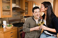 Couple in kitchen holding wine, woman kissing man on forehead