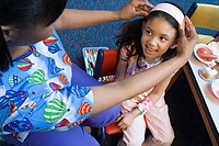 Nurse putting headband on girl