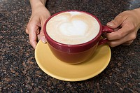 Person holding cappuccino