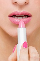 Woman applying pink lipstick (thumbnail)