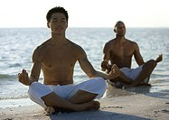 Two men meditating on beach