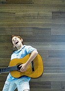 Boy playing guitar and singing with emotion