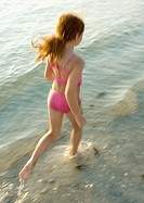 Girl running in surf at beach