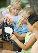 Group of children looking at notebook together