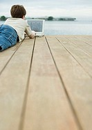 Boy lying on dock, using laptop