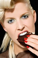 Woman biting a slice of cake