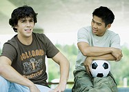 Two male students, one with soccer ball