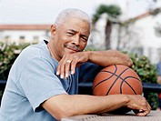 Portrait of a Senior Man Leaning on a Basketball