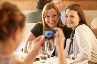 Two women in restaurant being photographed by female friend, smiling