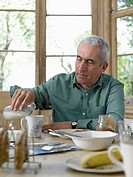 Senior man sitting at breakfast table, pouring milk into mug