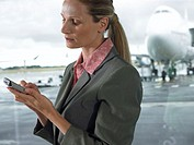Businesswoman using palm top in airport, close-up